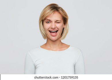 Indoor photo of happy winksing flirting attractive blonde woman with short stylish haircut, shows tongue, wears tight long sleeve t shirt isolated over white background