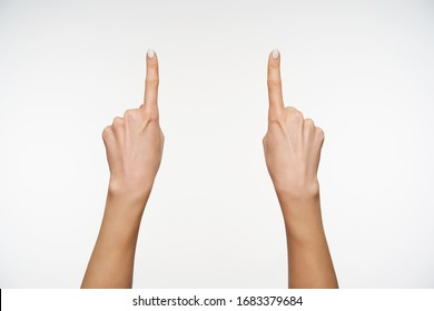 Indoor photo of pretty woman's hands keeping forefingers raised while pointing upwards, isolated over white background while expressing body language