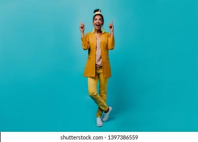 Indoor photo of refined black woman looking up. Studio shot of romantic girl wears yellow costume.