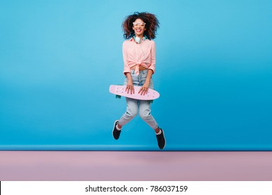 Indoor photo of relaxed african woman in cotton pink shirt dancing with longboard in blue studio. Portrait of jumping curly girl with brown skin enjoying photoshoot with skateboard in summer.
