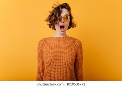 Indoor photo of romantic shocked woman in trendy sunglasses standing near yellow wall. Portrait of dreamy white girl with wavy hair expressing amazement.