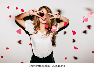 Indoor photo of stunning european lady in red sunglasses having fun at home party. Lovely girl in white t-shirt fooling around under heart confetti.