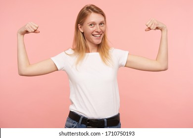 Indoor photo of young pretty redhead lady dressed in basic white t-shirt smiling broadly at camera while demonstrating her strong bicepses, posing over pink background