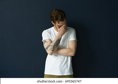 Indoor picture of attractive shy embarrassed young man with beard and tattoo on right arm making faceplam gesture, feeling shamed about something. Human reaction, feelings and attitude concept