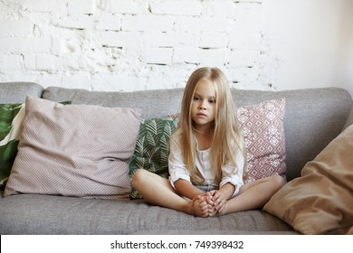 Indoor picture of beautiful unhappy sad little 5-year old girl sitting cross legged on couch in living room, feeling bored and lonely, being home alone while her parents spending all day at work