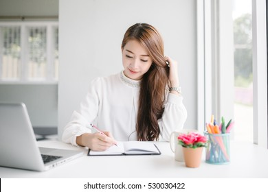 indoor picture of smiling Asia woman writing with notebook and pen