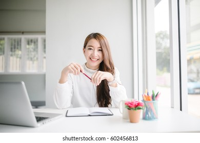 indoor picture of smiling Asia woman with notebook and pen