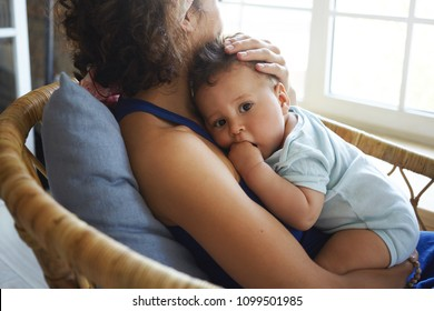 Indoor picture of unrecognizable young dark skinned female sitting in armchair, holding cute adorable toddler, stroking his hair. Lovely infant resting in mother's hands, looking at camera