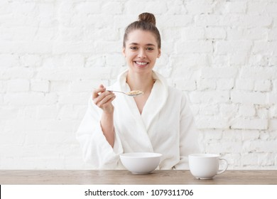 Indoor picture of young European Caucasian lady sitting in white bathrobe at table eating cereals and drinking coffee or tea for breakfast looking smiling at camera feeling positive and relaxed