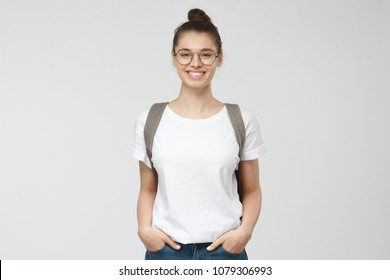 Indoor picture of young good-looking teenage girl isolated on gray background in white casual T-shirt, wearing glasses and gray backpack and jeans, feeling relaxed and positive, willing to walk