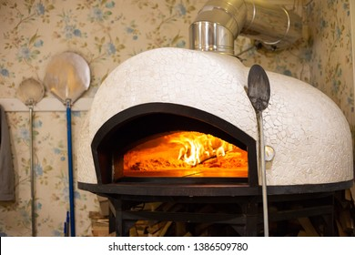 Indoor pizza oven with burning fire inside and a pizza peel or shovel leaned over aside and two other shovels in the background. Hacked firewood logs can be seen below the oven
