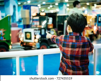 At a Indoor Playland and Playground Park for learning, A boy was enjoying to see the electric trains on background