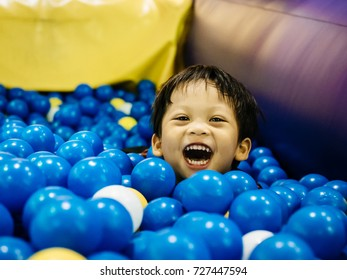 At a Indoor Playland and Playground Park for learning, A boy was enjoying to play plastic slider player on background.