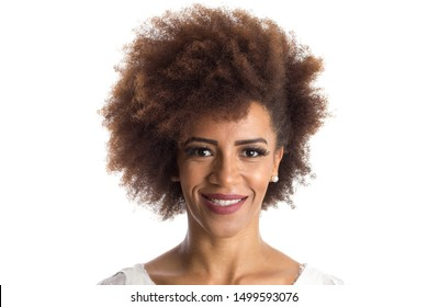 Indoor portrait of african american woman looking happily in camera. Standing against white background.