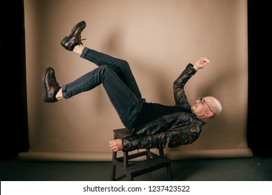 Indoor portrait of artistic adult unusual male. Funny bald man in biker leather jacket and oxford shoes. Fashion clothes. Stylish weird boy falling down from chair on brown background. Doing exercices