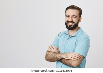 Indoor portrait of attractive adult man with beard and shiny smile, standing over gray background half-turned with crossed arms. Guy assures with his look that he is reliable and very grounded.