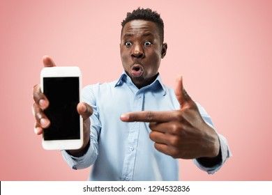 Indoor portrait of attractive young black african man isolated on pink background, holding blank smartphone, smiling at camera, showing screen, feeling happy and surprised. Human emotions, facial
