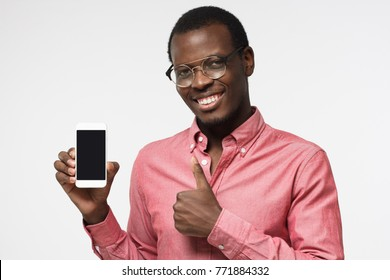Indoor portrait of attractive young black man isolated on grey background, holding blank smartphone, smiling at camera, showing thubms up gesture, feeling happy