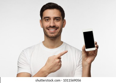 Indoor portrait of attractive young man isolated on grey background, holding blank smartphone, smiling at camera, feeling happy
