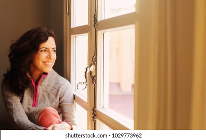 Indoor portrait of beautiful 45 years old woman next to the window