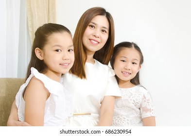 Indoor portrait of beautiful asian mother and daughters