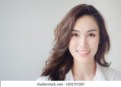 Indoor portrait of beautiful brunette young woman with smiling cheerfully, showing her white teeth to camera with copy space