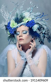 Indoor portrait of beautiful woman dressing like fantasy character wearing bluish dress and floral crown