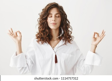 Indoor portrait of calm beautiful caucasian woman meditating in white blouse, smiling while raising hands with zen gestures, standing against gray background. Girlfriend dragged girl to yoga classes