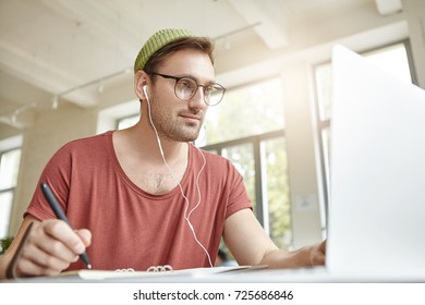 Indoor portrait of casually dressed young Caucasian male with beard having joyful look while relaxing at cafe using laptop, watching film with original subtitles, making pause to write down new words