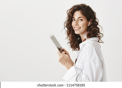 Indoor portrait of charming cute caucasian woman with tender smile standing in profile with tablet in hands and wireless earphone in ear, smiling broadly at camera. Girl seeks yoga video lessons
