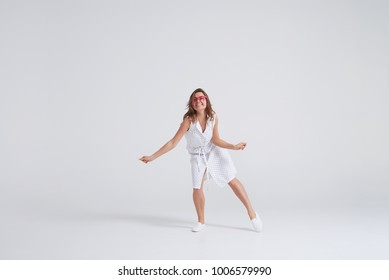 Indoor portrait of charming young woman in dress having fun at studio