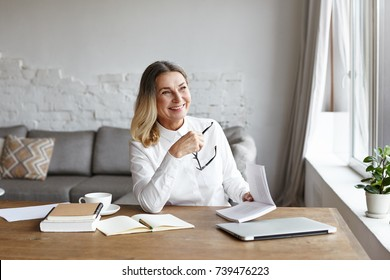Indoor portrait of cheerful middle aged female chief editor with thick loose hair sitting at her workplace and laughing while reading satirical verses, holding book, enjoying author's writing style