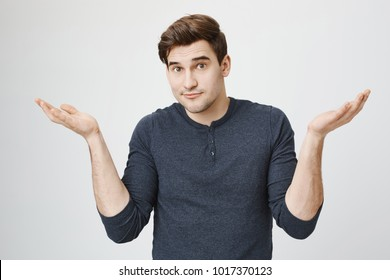 Indoor portrait of confused handsome guy showing I have no idea gesture, shrugging shoulders and raising hands, standing against gray background. Sorry I did not know it was your food in fridge