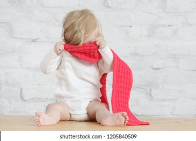 Indoor portrait of a cute blond baby wearing a red wool shawl, playing a peekaboo game or don't want to dress up concept