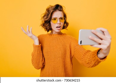 Indoor portrait of disappointed short-haired girl in glasses making selfie in studio. Upset young woman in knitted sweater waving hand during video call, holding smartphone on yellow background.