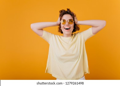 Indoor portrait of excited young lady in oversize yellow t-shirt touching her head. Studio shot of emotional caucasian girl happy laughing.