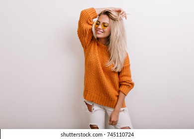 Indoor portrait of glad fair-haired girl wearing ripped jeans and round yellow glasses. Smiling blonde woman in stylish knitted cardigan posing with eyes closed and hand up.