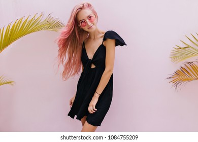Indoor portrait of good-looking tanned girl with pink wavy hair. Lovable european lady posing on light background in trendy black dress.