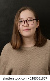 Indoor portrait of graceful smiling Mongolian girl with glasses on black background. Friendly person concept. Young student with a woolen jumper.