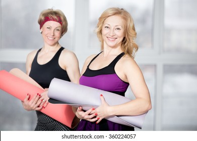 Indoor portrait of group of two cheerful attractive fit senior women posing holding fitness mats, working out in sports club class, happy smiling, looking at camera with friendly expression