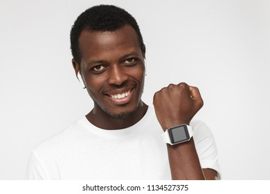 Indoor portrait of handsome African American man isolated on gray background wearing white casual T-shirt and showing smart wristwatch on wrist with confident smile satisfied with his lifestyle