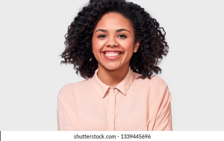 Indoor portrait of happy African American young woman, dressed in casual beige shirt, smiles pleasantly at camera, rejoices positive emotions, standing against white studio wall.