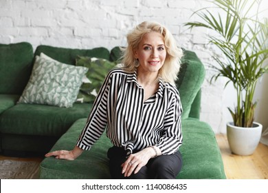 Indoor portrait of luxurious glamourous attractive European woman in her sixties with blonde hair and fit body looking at camera with pleased friendly smile, sitting on comfortable green couch
