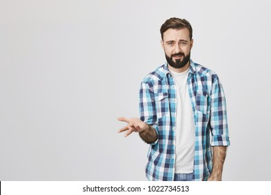 Indoor portrait of mad puzzled guy spreading hand showing puzzled gesture, over gray background. Person can not understand why everyone is bothered so much. Maybe it is not a big deal