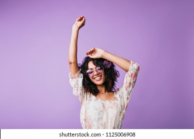 Indoor portrait of magnificent african woman standing on purple background with hands up. Studio shot of  female model with wavy hair expressing good emotions.