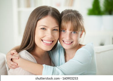 Indoor portrait of a mother and daughter hugging.