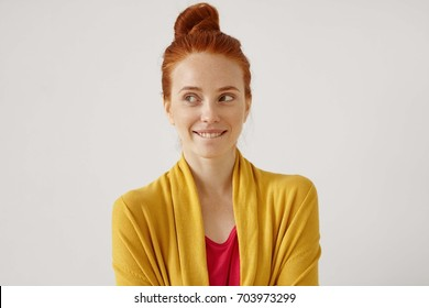 Indoor portrait of mysterious charming young European gimger female with hair knot looking sideways with enigmatic smile, biting her lips while planning surprise birthday party for her husband
