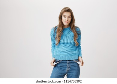 Indoor portrait of sad and gloomy cute caucasian female showing empty pockets while standing over gray background. Woman spent all her savings yesterday on sale day. Girl can not afford anything