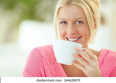 Indoor portrait of a smiling Caucasian woman drinking tea.
