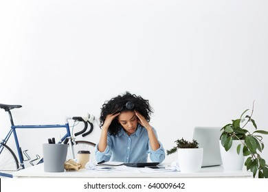 Indoor portrait of tired overworked young businesswoman feeling stressed while facing a problem, doing accounts and calculating expenses by herself, squeezing her head. People, business and paperwork